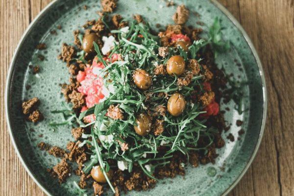 Dakos Salat auf einem günen Teller